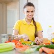 Woman in yellow chopping  vegetables   — Foto de Stock