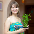 Girl with lucky bamboo plant — Stock Photo #27493175