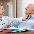 Doctor touching  neck of  senior man — Stock Photo