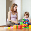 Stock Photo: Pregnant mother plays with child in home