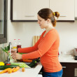 Woman washing vegetables in kitchen — Stock Photo #27493685