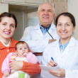 Stock Photo: Mother with three months baby and pediatricidoctors