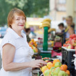 Mature woman chooses fruits   — Stock Photo