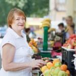 Mature woman chooses fruits — Stock Photo #27493797