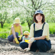 图库照片: Women with child works at vegetables garden