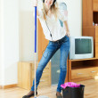 Stock Photo: Cheerful womin headphones washing floor with mop