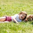 Happy   child playing with puppy at  meadow in summer — Stock Photo