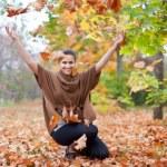 Woman throws autumn leaves — Stock Photo