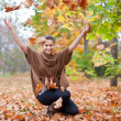Woman throws autumn leaves — Stock Photo