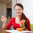 Long-haired woman in red eats grapefruit — Stock Photo #27494085