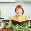 Stockfoto: Mature womcooking with cookery book