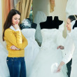 Saleswoman helps girl chooses white bridal outfit — Stockfoto
