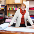 Stock Photo: Salesclerk measures fabric
