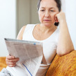 Stock Photo: Wistful mature womlooks newspaper