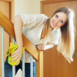 Happy pretty girl dusting stair railings — Stock Photo #27494901