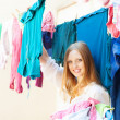 Stock Photo: Womhangs clothes to dry