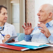 Mature doctor talks with sick senior man — Stock Photo