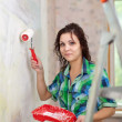Girl paints wall with roller — Stock Photo
