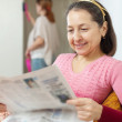 Stock Photo: Mature womreads newspaper during daughter cleans at home