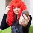 Woman in red periwig — Stock Photo