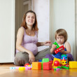 Happy pregnant mother plays with child — Stock Photo