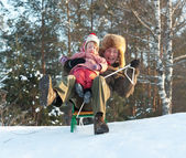 Happy man with child doing downhill on sleigh — Stock Photo