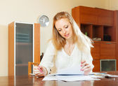 Serious blonde woman looking financial documents — Stock Photo