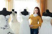 Smiling woman chooses wedding dress — Stok fotoğraf