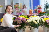 Happy woman with chrysanthemum at store — Stock Photo