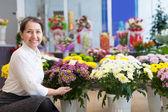 Szczęśliwa kobieta z chryzantemy w sklepie — Zdjęcie stockowe