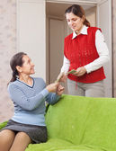 Adult daughter gives mature mother the money — Stock Photo
