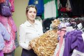 Female buyer chooses gilded dress — Stock Photo