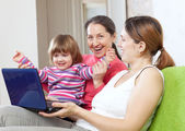 Happy family of three generations with laptop — Stock Photo