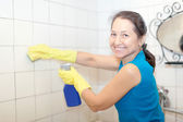 Smiling woman cleans tile — Stock Photo