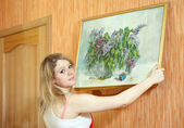 Woman hangs picture on wall at home — Stock Photo