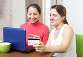 Daughter helps the mother buying online with laptop — Stock Photo