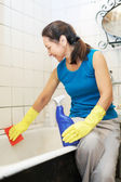 Mature woman cleans bathroom with cleaner — Stock Photo