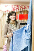 Woman chooses draperies — Stock Photo
