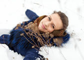 Woman lying in coat on the snow — Stock Photo