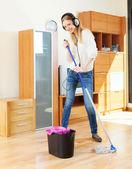 Girl in headphones washing floor with mop — Stock Photo
