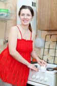 Mulher de vermelho limpa fogão a gás com esponja de melamina — Foto Stock