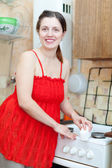 Woman in red cleans gas stove with melamine sponge — Foto Stock