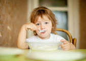 Child eats dairy with spoon — Stockfoto