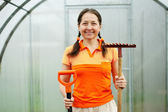 Woman with garden tools in greenhouse — Stock Photo