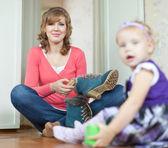 Femme avec bébé nettoie chaussures — Photo