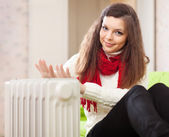 Woman warms hands near radiator — 图库照片