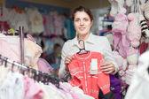 Woman chooses children wear — Stock Photo