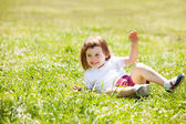 Happy child playing at grass meadow — Stock Photo