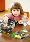Child eats mussels in home — Stock Photo