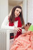 Woman reads e-book near heater — Stock Photo